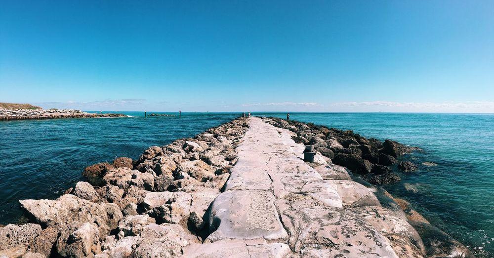 Groyne In Sea Against Blue Sky