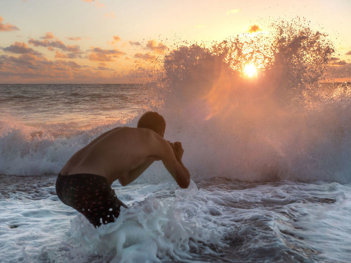 Rear view of shirtless man photographing huge wave at beach during sunset
