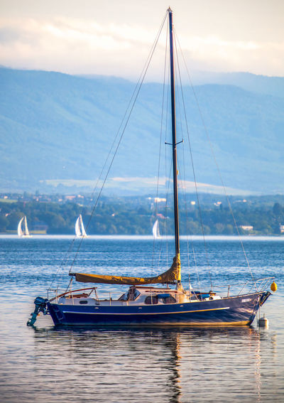 Boat on sea against mountain