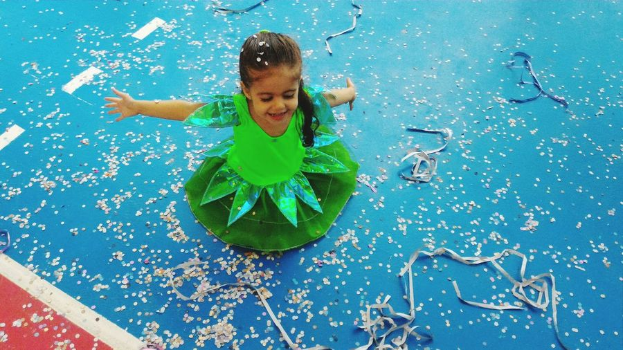 High angle view of happy girl wearing costume enjoying in confetti