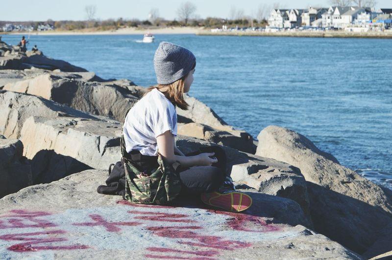 Girl Sitting On Rock At Seaside