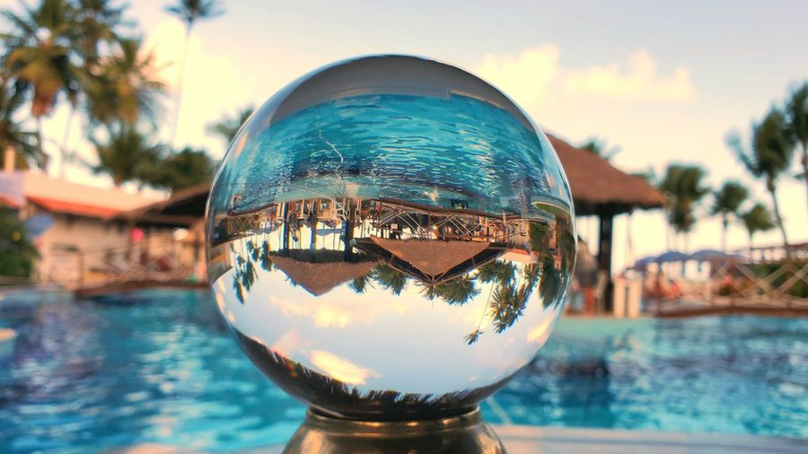 Close-up of crystal ball against swimming pool