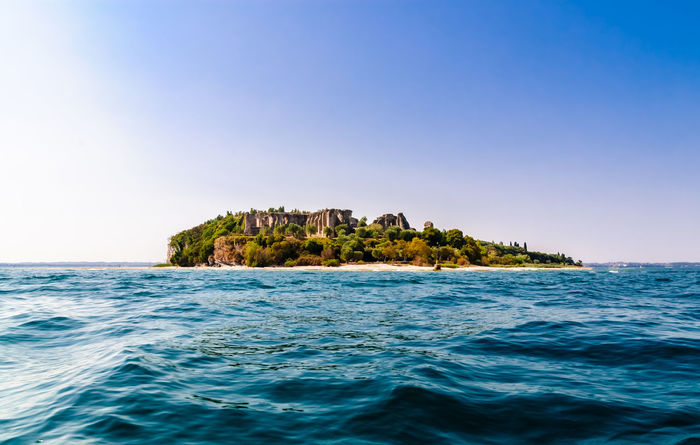 The tip of the Sirmione peninsula, at Lake Garda. Architecture Beach Beauty In Nature Blue Catullo Clear Sky Day Distant Empire Garda Horizon Over Water Lake Nature No People Outdoors Peninsula Rock - Object Roman Ruins Scenics Sea Sky Tropical Climate Vacations Waves