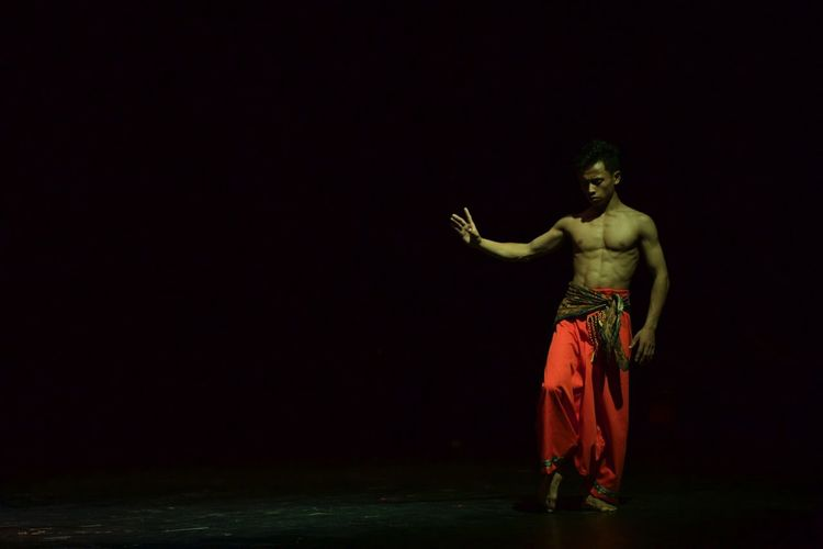 Shirtless young man performing on stage in dark