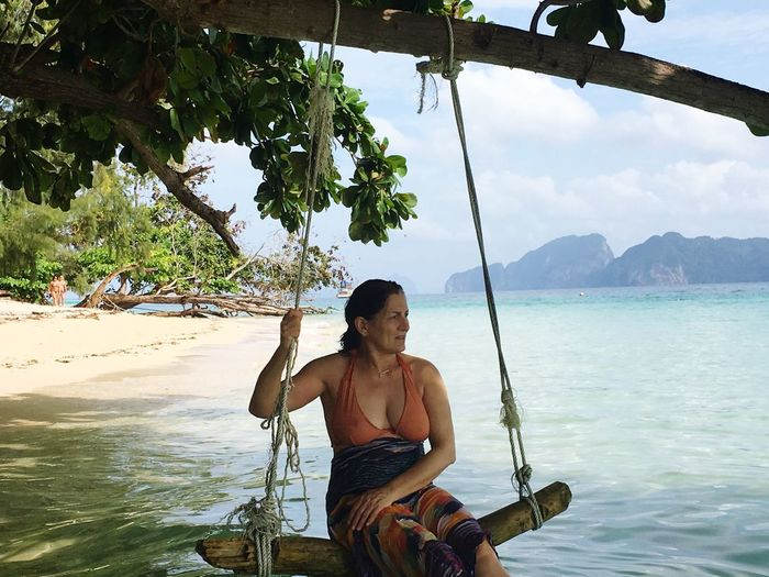 Mature woman looking away while swinging over sea against cloudy sky