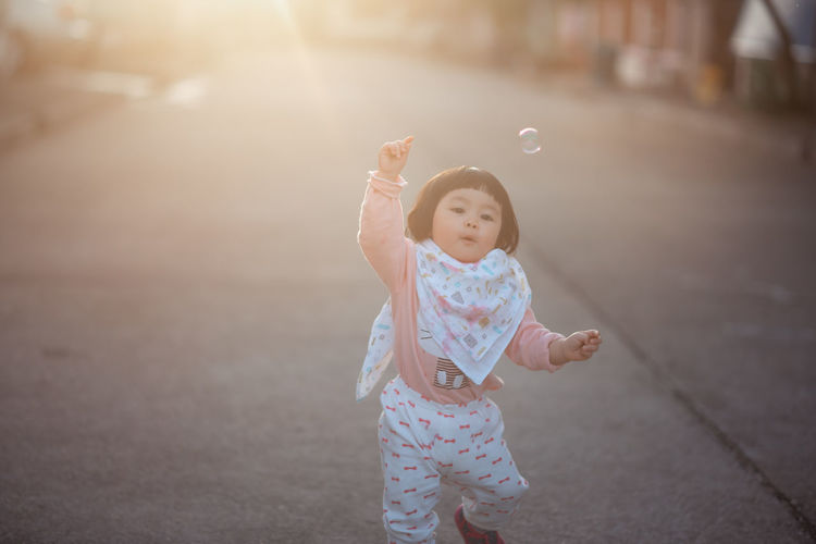 Cute girl looking at bubbles while standing on road