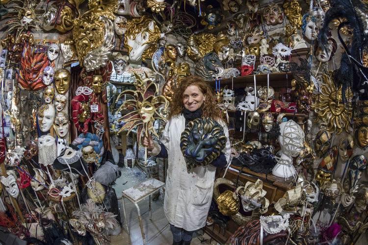 Marilisa Dal Cason, the artist performs traditional Venetian masks made of hand-made mache paper, Venetian carnival costumes and high-quality souvenirs. They can be found in Venice at San Polo Street. Art And Craft Artisan Artist Carnival Craftsman Venetian Workshop Abundance Carnival Masks Choice Craftsmanship  For Sale Large Group Of Objects Looking At Camera One Person One Woman Only Portrait Retail  Shop Standing Store Traditional Art Variation Venetian Mask Venetian Masks