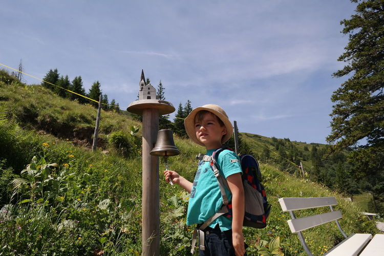 Boy with back pack ringing bell on landscape