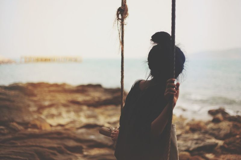 Young woman on swing looking at sea