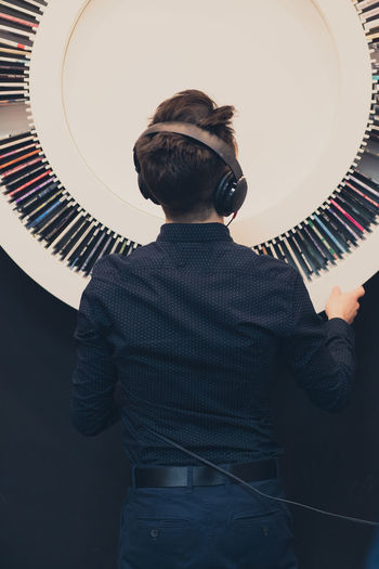Rear view of teenage boy listening music while standing against decoration