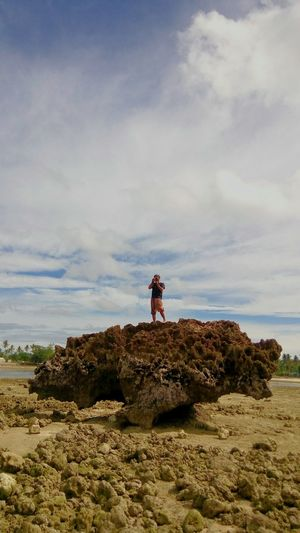 Woman photographing while standing on rock against sky
