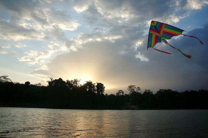A kite flying by the riverside during sunset Sunset Water No People Outdoors Sky Day Kite Fly Riverside Outdoor