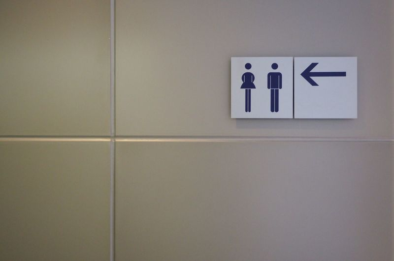 Close-up of restroom signs on tiled wall