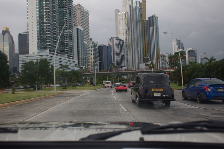 Cars on road against buildings in city