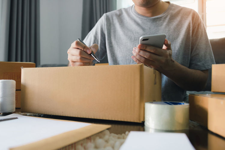Midsection of man writing on cardboard box while holding mobile phone at home