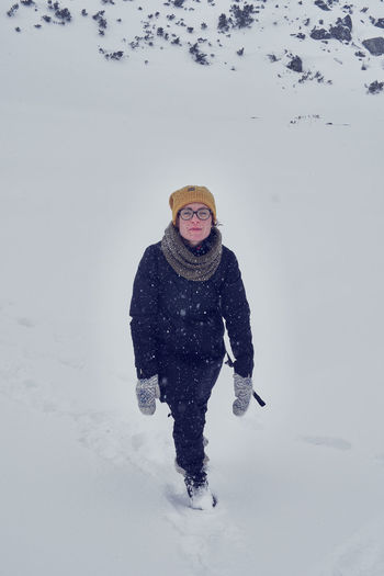 Young woman standing on snow against sky
