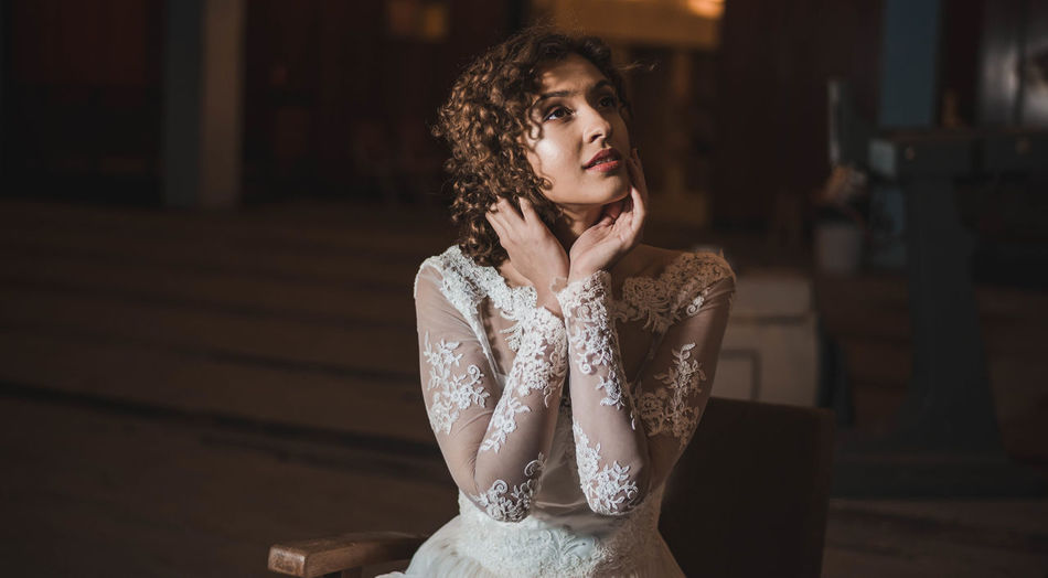 Sensuous woman in wedding dress sitting with head in hands at home