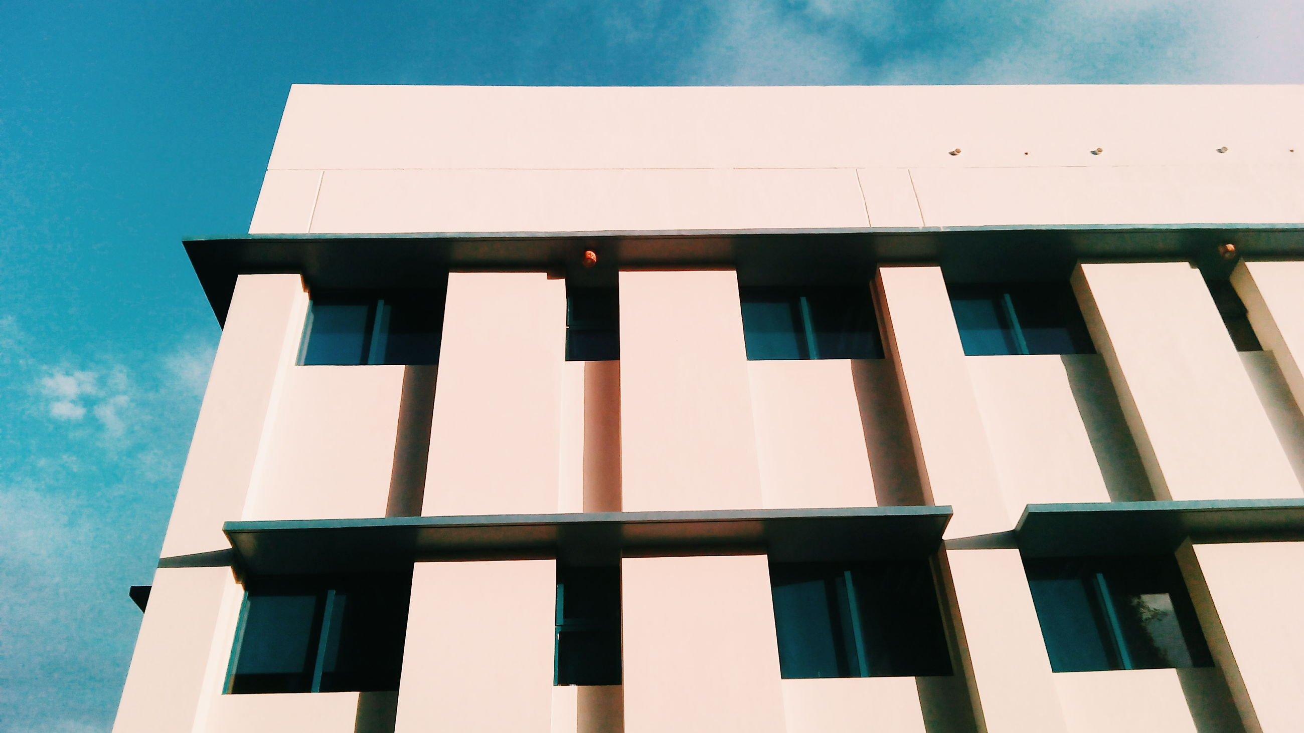 architecture, built structure, building exterior, low angle view, window, sky, day, outdoors, blue, cloud - sky, no people, building story