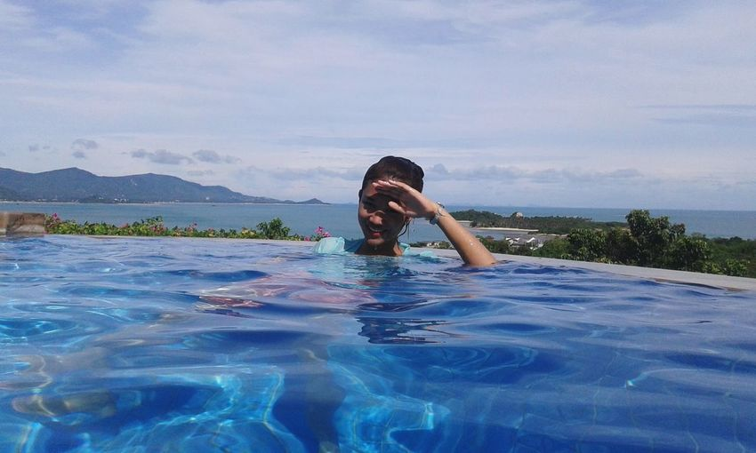 Portrait of young woman in infinity pool