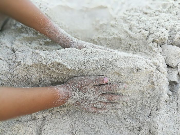 Cropped hands making sandcastle at beach