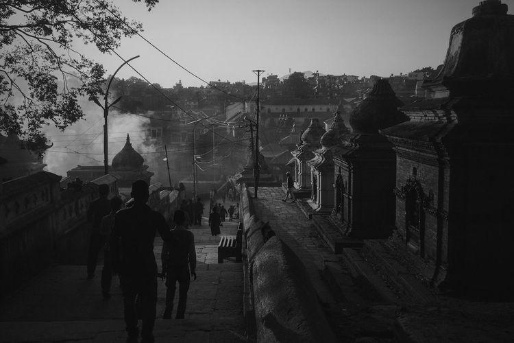 Rear view of men standing on street against sky