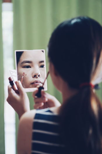 Reflection of woman applying make-up in mirror at home