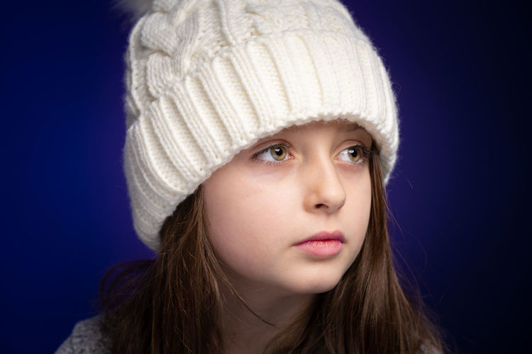 Smiling girl wearing knit hat looking away against purple background