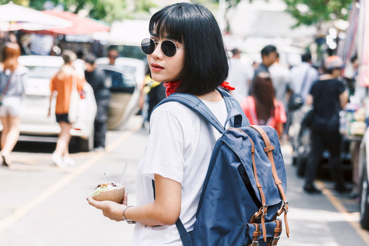 Portrait of young woman having snack on city street in city