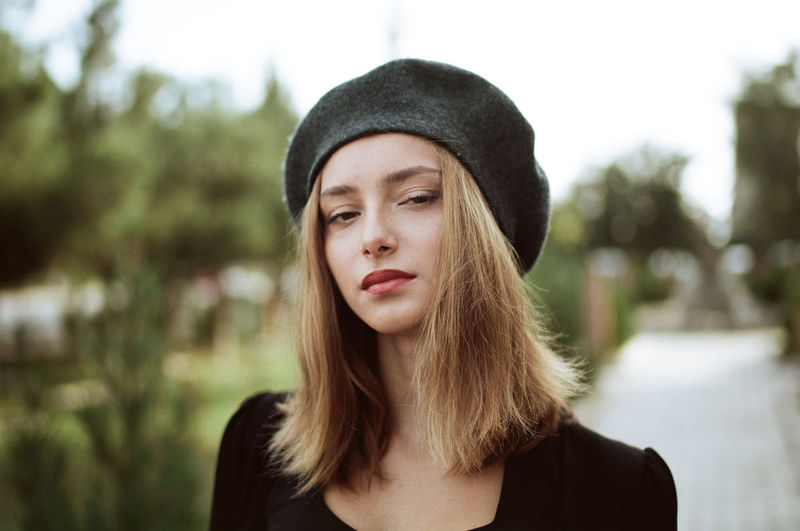 Close-up portrait of young woman wearing hat standing against sky at park
