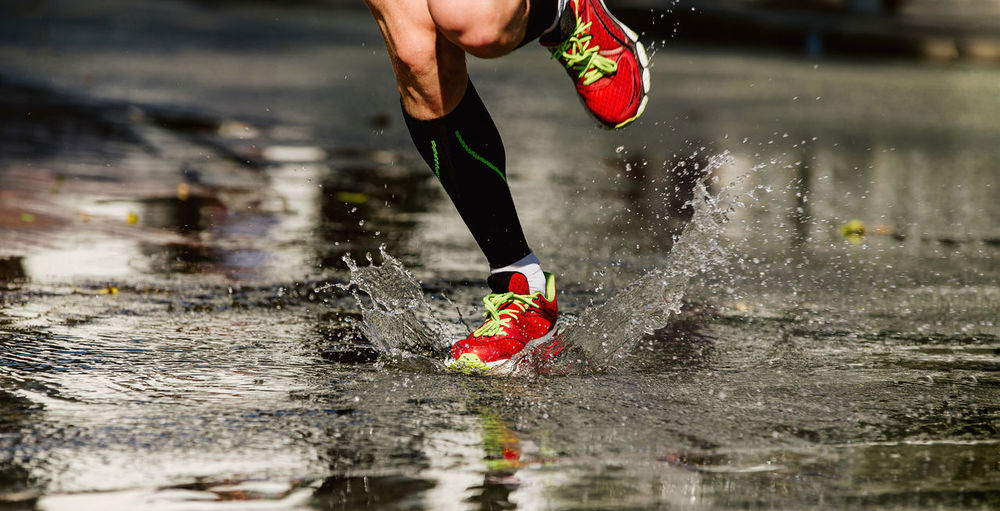 Low section of man splashing water while running on puddle