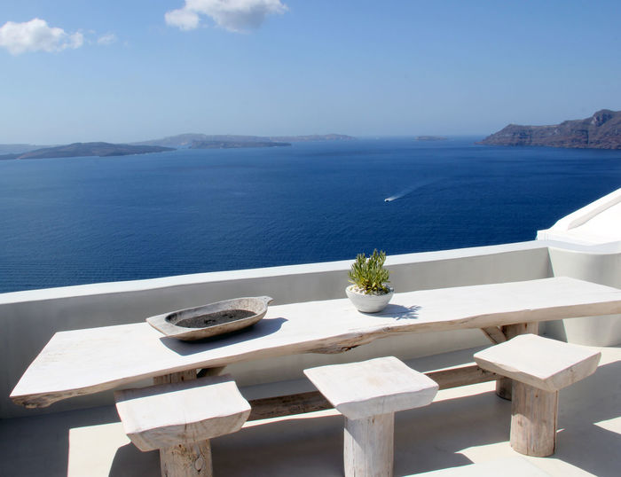 High angle view of table and seat on terrace against sea at santorini