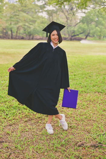 Portrait of young woman in graduation gown holding file while standing at park