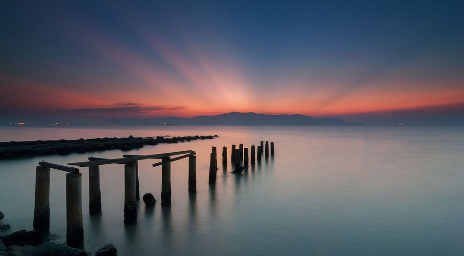 Amazing scenery during sunset with rays of light in the sky at old wooden jetty Robina Beach, Penang. (blurry soft focus noise silky water due to long exposure technique) Pier Rays Of Light Sunset_collection Abandoned Beach Beauty In Nature Day Evening Jetty Mountain Nature Ocean Outdoors Penang Malaysia Robina Scenics Sea Seascape Silky Water Sky Sunset Tranquil Scene Tranquility Water Wooden Post