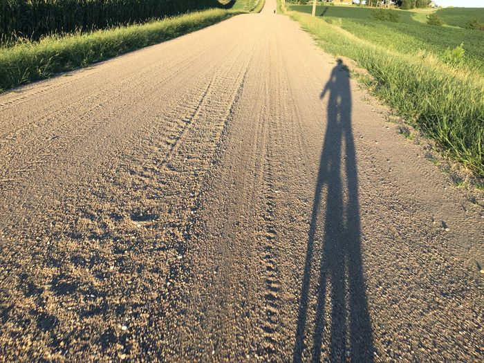 Shadow of cyclist on country road