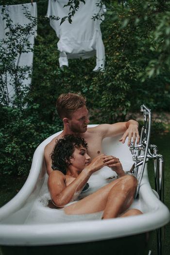 Couple in bathtub outdoors