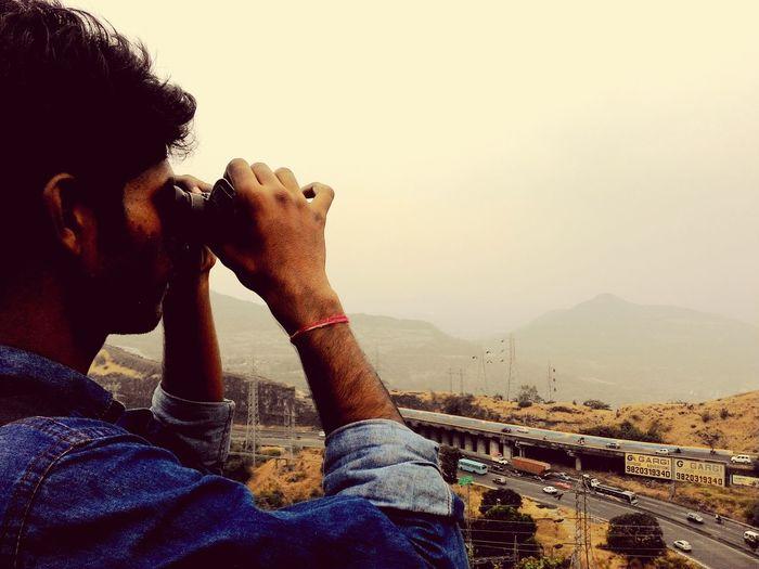 Man Looking Through Binoculars Against Sky