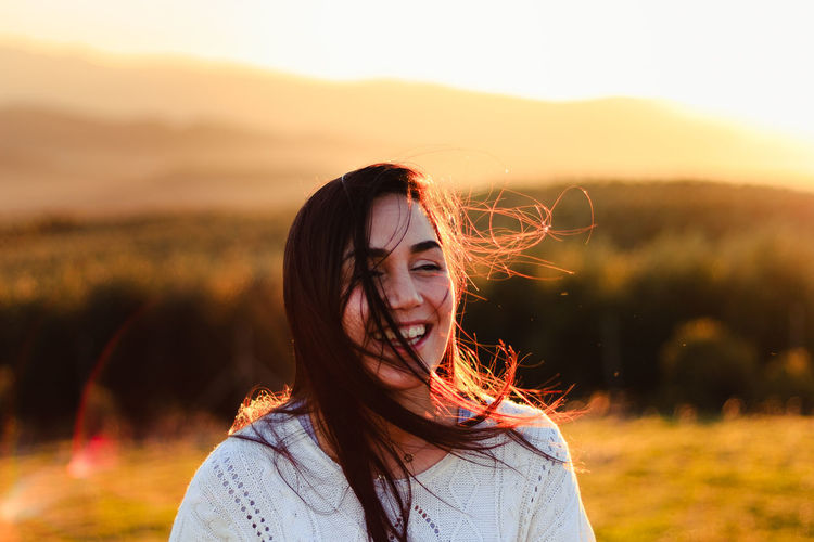 Close-Up Of Woman Smiling On Field Against Sky During Sunset