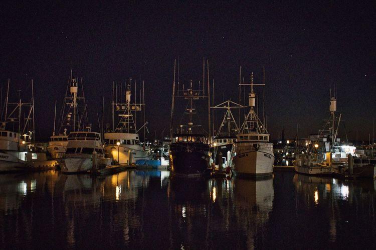 Sailboats moored in harbor at night
