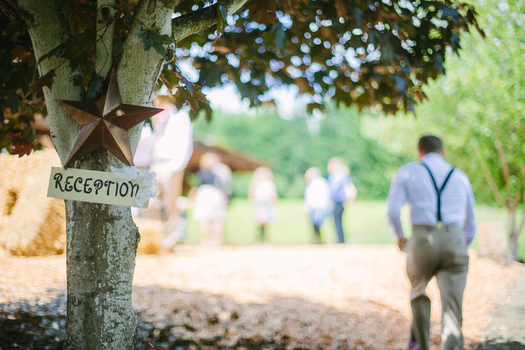Sign Board On Tree With People In Background At Reception