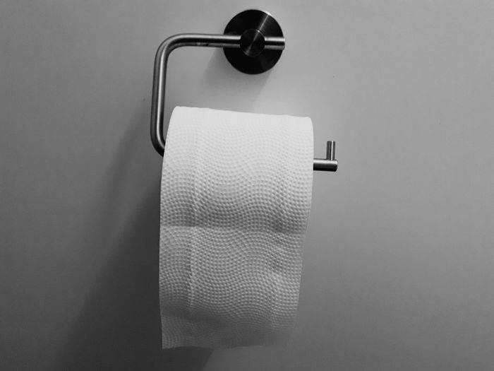 Close-up of toilet paper hanging in bathroom