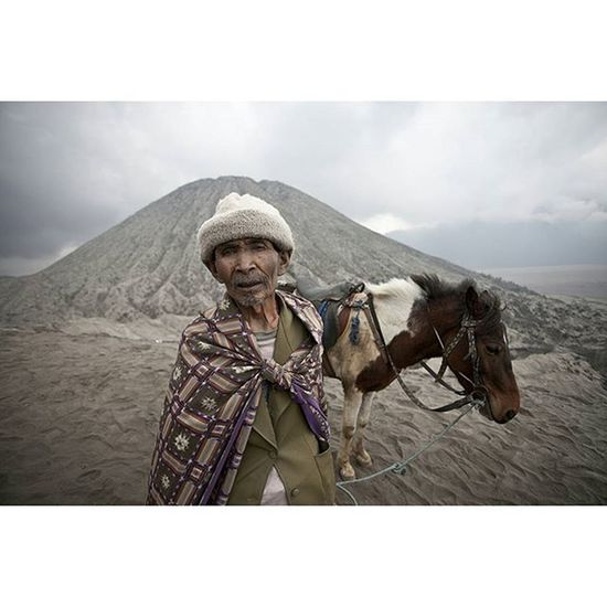 A Tenggerese man and his horse stand on top of Mount Bromo. Java INDONESIA Photooftheday Picoftheday photojournalism asia everydayasia ontheroad instagood reportage documentary humaninterest photodocumentary volcano nature horses landscape portrait ontheroad