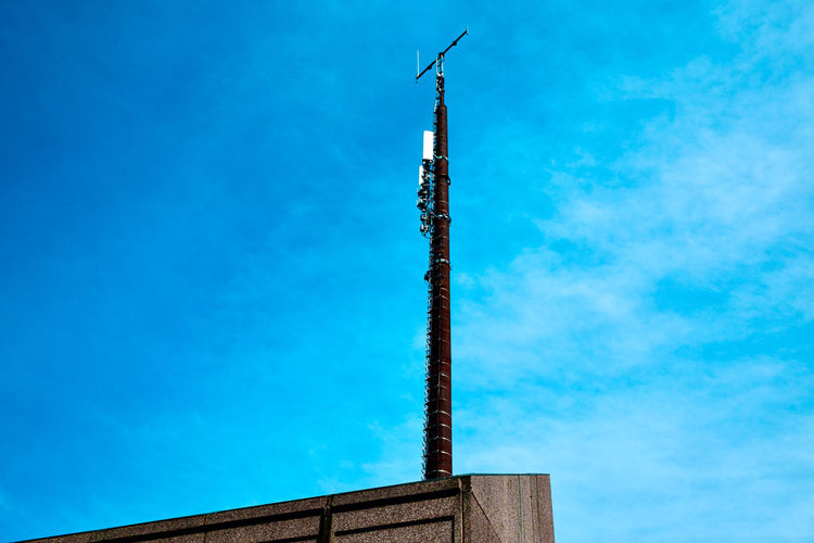 Low angle view of communications tower and building against sky