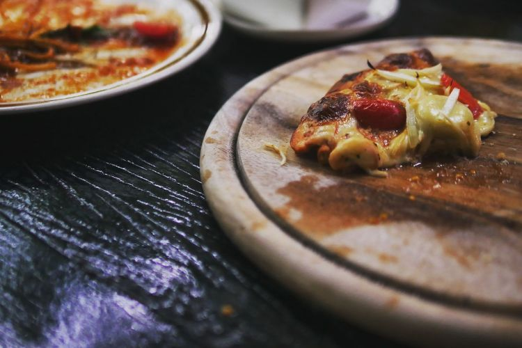 Close-up of pizza on serving board at table