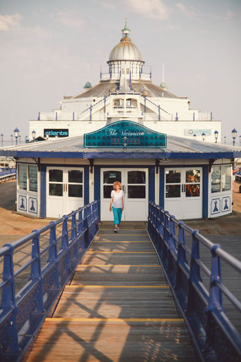 Woman walking on eastbourne pier against sky