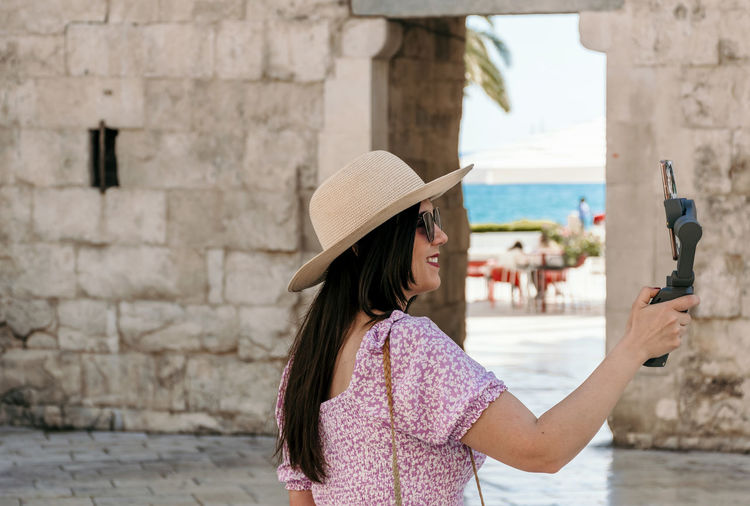Woman photographing with umbrella standing against built structure