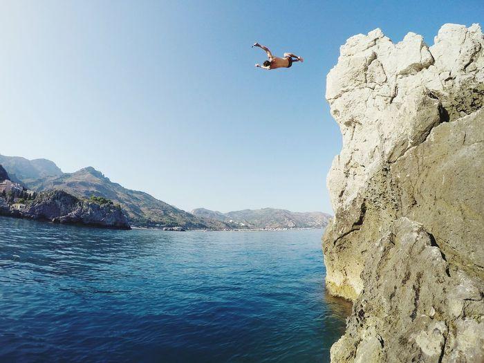 Man diving in lake against clear sky