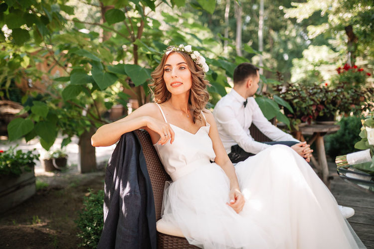 Bride and bridegroom sitting at park