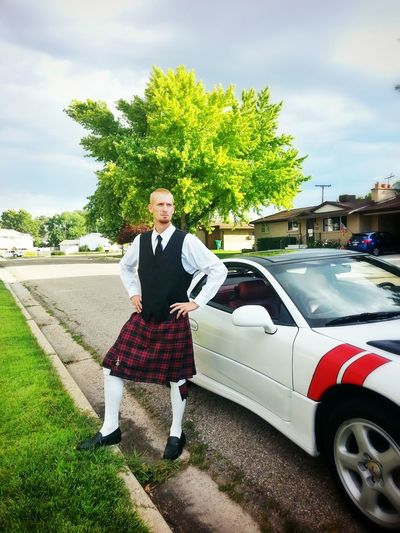Man in traditional clothing standing by car on road
