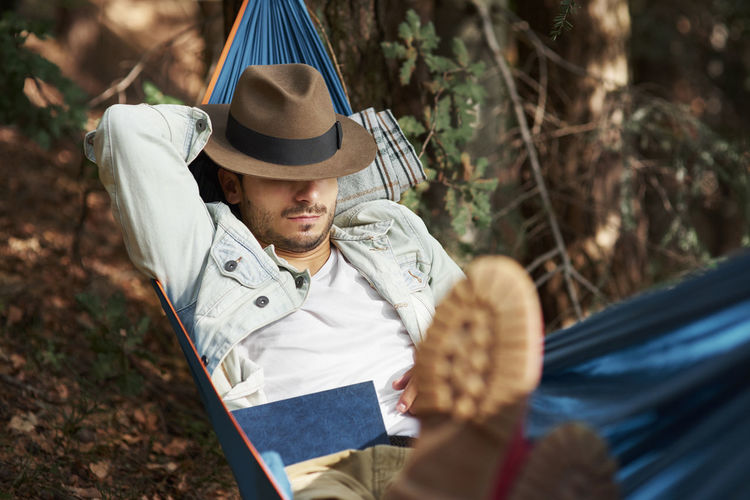 Man Wearing Hat Resting In Hammock At Forest