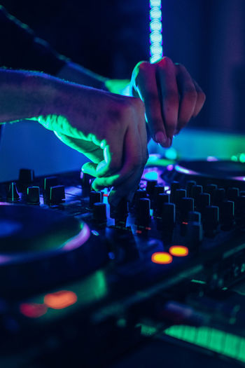 Cropped hand of man working on sound mixer in nightclub